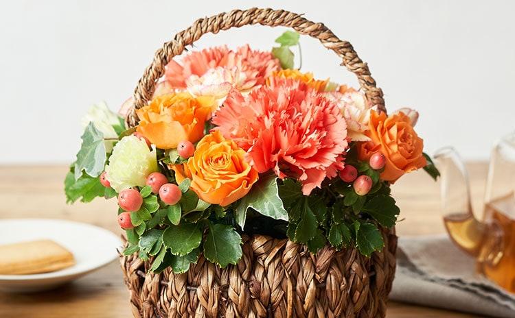 オレンジ色のカーネーションとバラの明るい雰囲気のブーケ:イメージ
